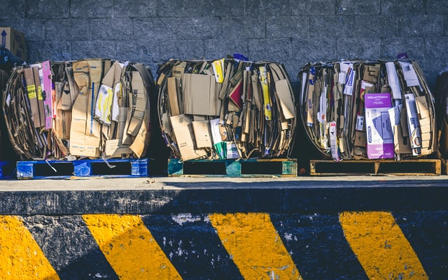 Bundles of cardboard recycling on wooden pallets ready to be recycled